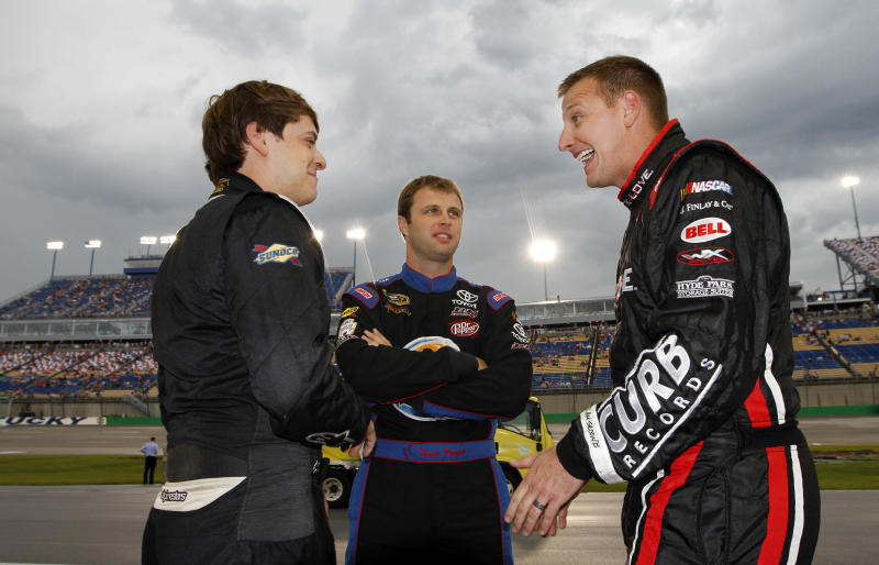 From left, drivers Landon Cassill, Travis Kvapil and Michael McDowell share stories during a rain delay before the NASCAR Sprint Cup auto race at Kentucky Speedway in Sparta, Ky., Saturday, June 29, 2013. (AP Photo/James Crisp)