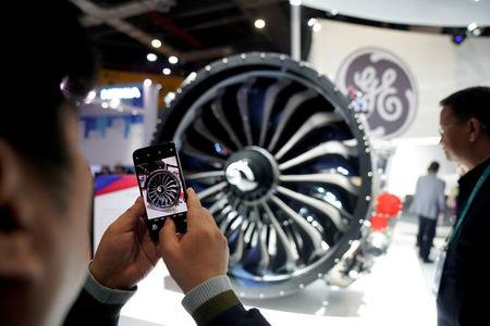 FILE PHOTO: A man takes a picture of a General Electric (GE) engine during the China International Import Expo (CIIE), at the National Exhibition and Convention Center in Shanghai