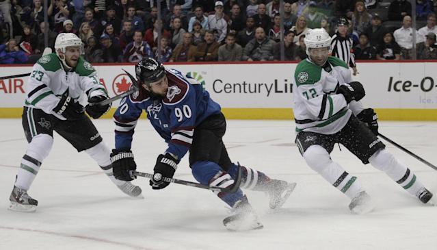 Colorado Avalanche center Ryan O'Reilly (90) shoots as Dallas Stars defenseman Alex Goligoski (33) and Stars right wing Erik Cole (72) defend in the third period of a hockey game in Denver on Tuesday, Oct. 15, 2013. Colorado won 3-2. (AP Photo/Joe Mahoney)
