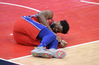 Philadelphia 76ers center Joel Embiid grimaces after an injury during the second half of the team's NBA basketball game against the Washington Wizards, Friday, March 12, 2021, in Washington. (AP Photo/Nick Wass)