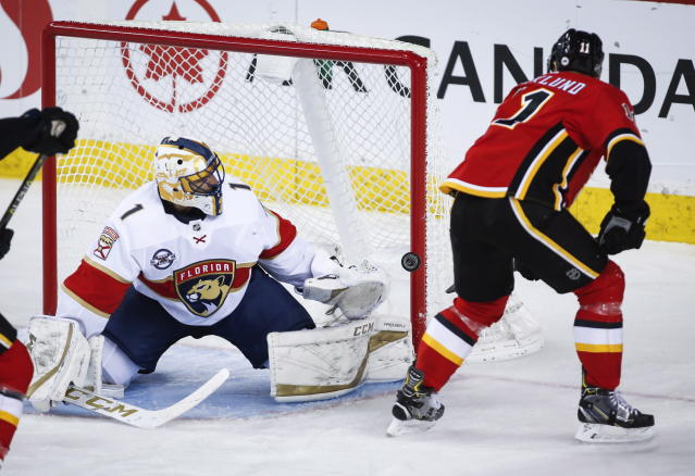 Florida Panthers goalie Roberto Luongo, left, watches as Calgary Flames' Mikael Backlund, of Sweden, hits the post during second-period NHL hockey game action in Calgary, Alberta, Friday, Jan. 11, 2019. (Jeff McIntosh/The Canadian Press via AP)