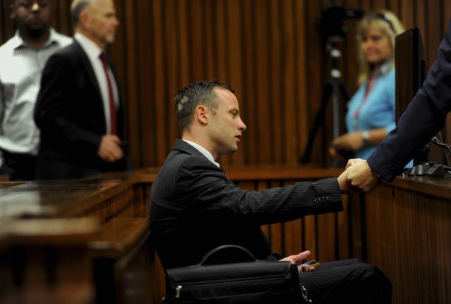 Olympic and Paralympic track star Oscar Pistorius sits in the dock during court proceedings at the North Gauteng High Court in Pretoria March 18, 2014. Pistorius is on trial for murdering his girlfriend Reeva Steenkamp at his suburban Pretoria home on Valentine's Day last year. REUTERS/Werner Beukes/Pool (SOUTH AFRICA - Tags: SPORT CRIME LAW ATHLETICS)
