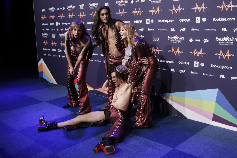 Members of the band Maneskin from Italy Thomas Raggi, from left, Ethan Torchio, Victoria De Angelis and Damiano David, on floor, pose for photographers with the trophy after winning the Grand Final of the Eurovision Song Contest at Ahoy arena in Rotterdam, Netherlands, Saturday, May 22, 2021. (AP Photo/Peter Dejong)