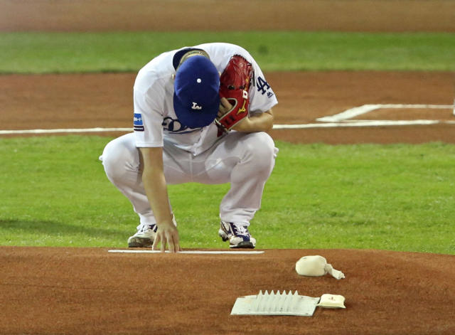 MLB All-Star starter Kenta Maeda of the Los Angeles Dodgers touches the mound before pitching against All Japan in Game 4 of their All-Stars Series baseball at Mazda Zoom-Zoom Stadium in Hiroshima, western Japan, Tuesday, Nov. 13, 2018. The stadium is Maeda's former home when he was playing for the Hiroshima Carp. (Kyodo News via AP)