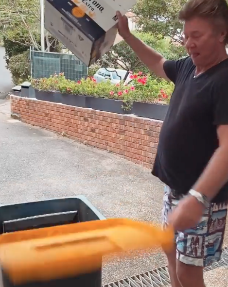 Richard Wilkins places Corona beer carton in recycling bin