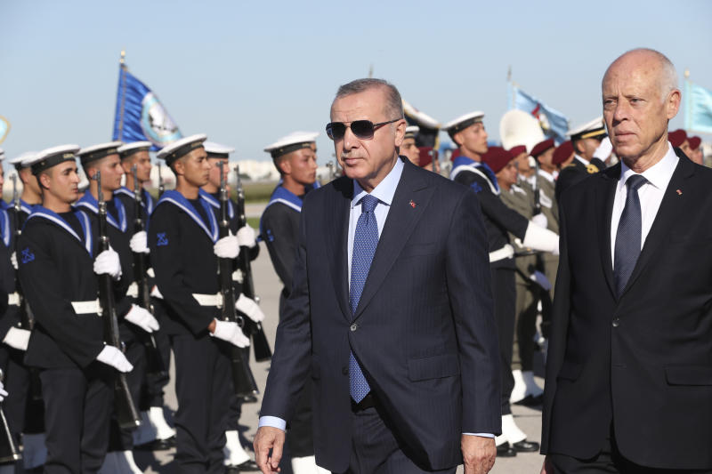 Turkey's President Recep Tayyip Erdogan, left, and Tunisian President Kais Saied review a honor guard at the airport, in Tunis, Tunisia, Wednesday, Dec. 25, 2019. Erdogan with top Turkish officials is on an unannounced visit to Tunisia to meet Saied. (Turkish Presidency via AP, Pool)