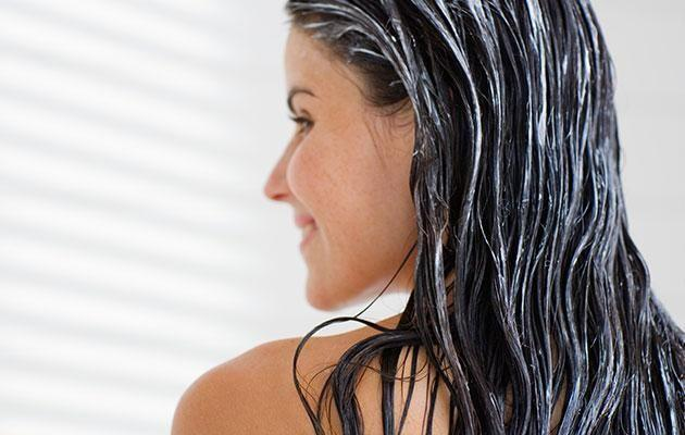 Once you've got conditioner in your hair, make sure you put it up and away from your skin. Photo: Getty images