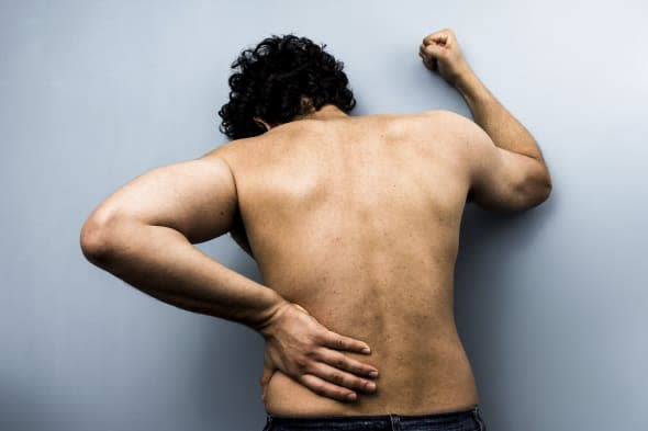 Young man with severe back pain from sciatica is banging his fist against the wall. Desaturated colors and high clarity help ill