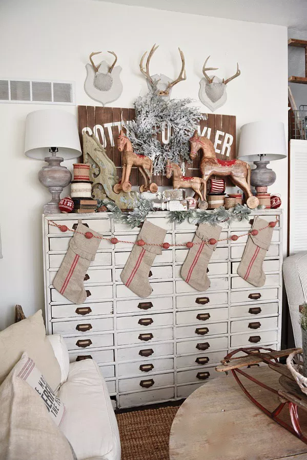 """<p>Don't have a fireplace or a staircase to attach your holiday stockings to? No worries! Blogger Liz Marie found a vintage <a href=""""https://go.redirectingat.com?id=74968X1596630&url=https%3A%2F%2Fwww.bedbathandbeyond.com%2Fstore%2Fproduct%2Fkate-and-laurel-wood-apothecary-drawer%2F3326702&sref=https%3A%2F%2Fwww.countryliving.com%2Fshopping%2Fg1407%2Fpersonalized-christmas-stockings%2F"""" rel=""""nofollow noopener"""" target=""""_blank"""" data-ylk=""""slk:card catalog"""" class=""""link rapid-noclick-resp"""">card catalog</a> and made it extra festive by painting it a lighter color and added horse figurines, a wintery sliver wreath and antlers.</p><p><strong>Get the tutorial at <a href=""""http://www.lizmarieblog.com/2015/11/vintage-rocking-horse-christmas-card-catalog/"""" rel=""""nofollow noopener"""" target=""""_blank"""" data-ylk=""""slk:Liz Marie Blog"""" class=""""link rapid-noclick-resp"""">Liz Marie Blog</a>.</strong></p><p><strong><a class=""""link rapid-noclick-resp"""" href=""""https://go.redirectingat.com?id=74968X1596630&url=https%3A%2F%2Fwww.bedbathandbeyond.com%2Fstore%2Fproduct%2Fkate-and-laurel-wood-apothecary-drawer%2F3326702&sref=https%3A%2F%2Fwww.countryliving.com%2Fshopping%2Fg1407%2Fpersonalized-christmas-stockings%2F"""" rel=""""nofollow noopener"""" target=""""_blank"""" data-ylk=""""slk:SHOP CARD CATALOGS"""">SHOP CARD CATALOGS</a><br></strong></p>"""