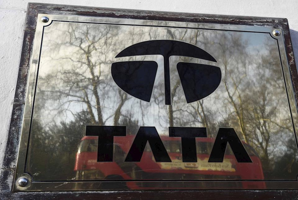 A bus is reflected in a Tata sign outside their offices in London