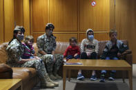 """Members of the Lebanese General Security forces sit with Albanian children during an operation to take them back home to Albania from al-Hol, northern Syria, at the Rafik Hariri International Airport in Beirut, Lebanon, Tuesday, Oct. 27, 2020. The repatriation of four children and a woman related to Albanian nationals who joined Islamic extremist groups in Syria """"is a great step"""" to be followed by more repatriations, Albania's prime minister said Tuesday. (AP Photo/Bilal Hussein)"""
