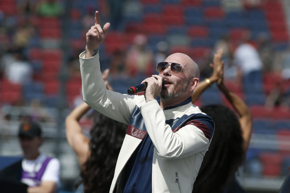 """FILE - Pitbull performs prior to a NASCAR Cup Series auto race at Phoenix Raceway in Avondale Ariz., in this Sunday, March 8, 2020, file photo. New NASCAR team Trackhouse Racing has brought entertainer Pitbull on as an ownership partner for an organization making its debut next month at the Daytona 500. """"Mr. Worldwide"""" joins NBA Hall of Famer Michael Jordan as celebrity owners entering NASCAR this year. (AP Photo/Ralph Freso, File)"""