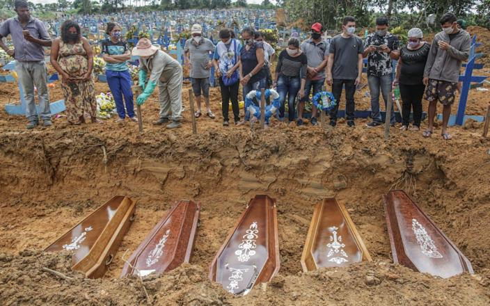 People wearing protective masks observe to the graves with the remains of their relatives during a mass burial of coronavirus victims - Getty Images South America