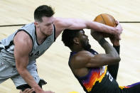 San Antonio Spurs forward Drew Eubanks (14) blocks the shot of Phoenix Suns center Deandre Ayton during the second half of an NBA basketball game Saturday, April 17, 2021, in Phoenix. (AP Photo/Rick Scuteri)