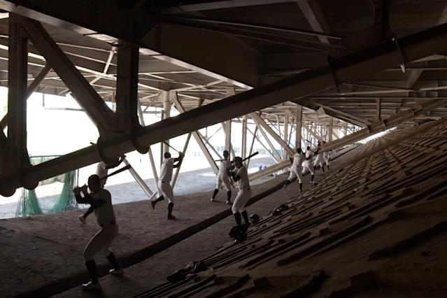Baseball players practicing under the bleachers