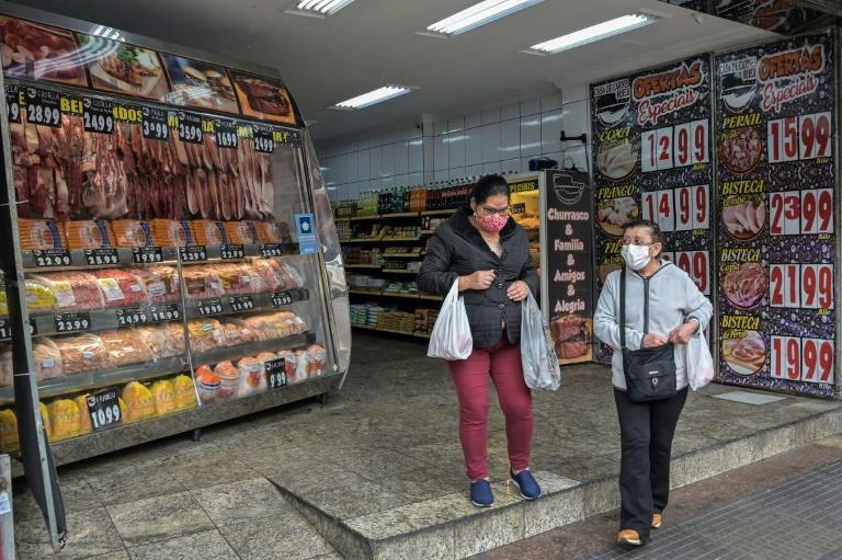 Women leave a butcher's shop in the Liberdade neighborhood in Sao Paulo, Brazil - prices of red meat have gone up three times that of the overall inflation rate (AFP/NELSON ALMEIDA)