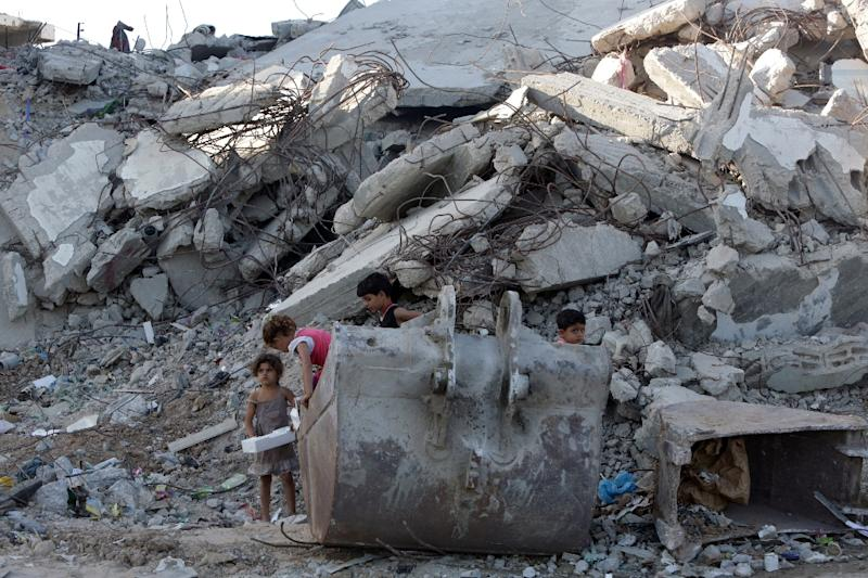 Palestinian children play in the rubble of buildings on June 22, 2015 in Gaza City, which were destroyed during the 50-day war between Israel and Hamas-militants in the summer of 2014 (AFP Photo/Mahmud Hams)