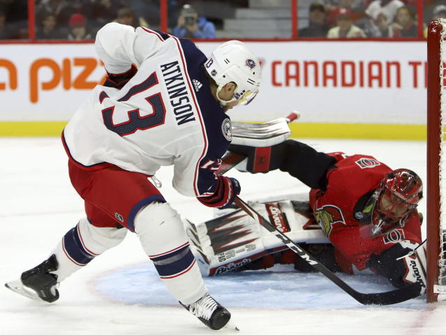 Columbus Blue Jackets right wing Cam Atkinson (13) scores on Ottawa Senators goaltender Anders Nilsson (31) during the first period of an NHL hockey game in Ottawa, Saturday, Dec. 14, 2019. (Fred Chartrand/The Canadian Press via AP)