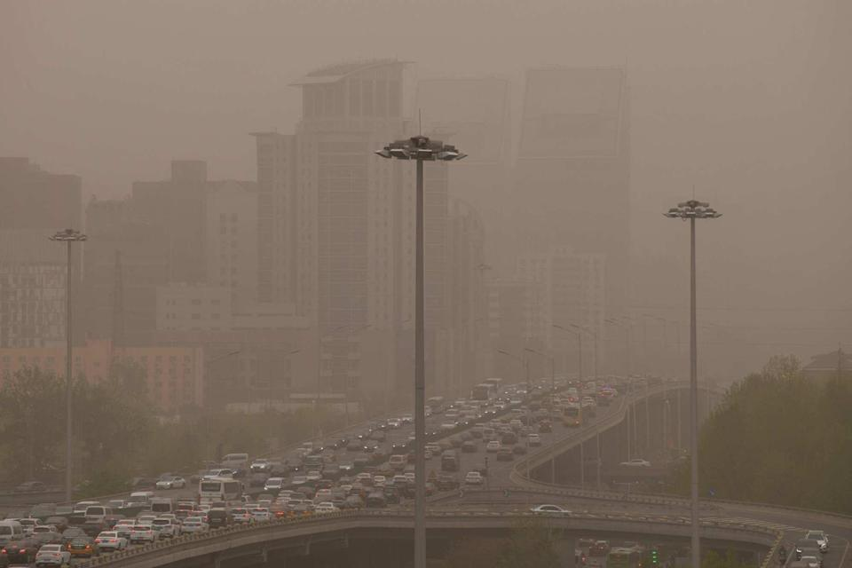 Motorists commute on a road during a sandstorm in Beijing on Thursday. Photo: AFP