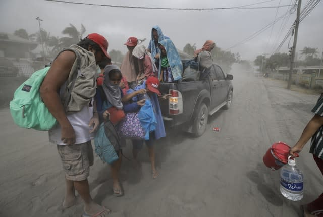 A family evacuates to safer ground in Tagaytay, Cavite province, southern Philippines (Aaron Favila/AP)