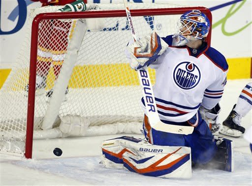 Edmonton Oilers goalie Devan Dubnyk looks back as the puck bounces off the post during the second period of an NHL hockey game against the Calgary Flames in Calgary, Alberta, Saturday, Jan. 26, 2013. (AP Photo/The Canadian Press, Jeff McIntosh)