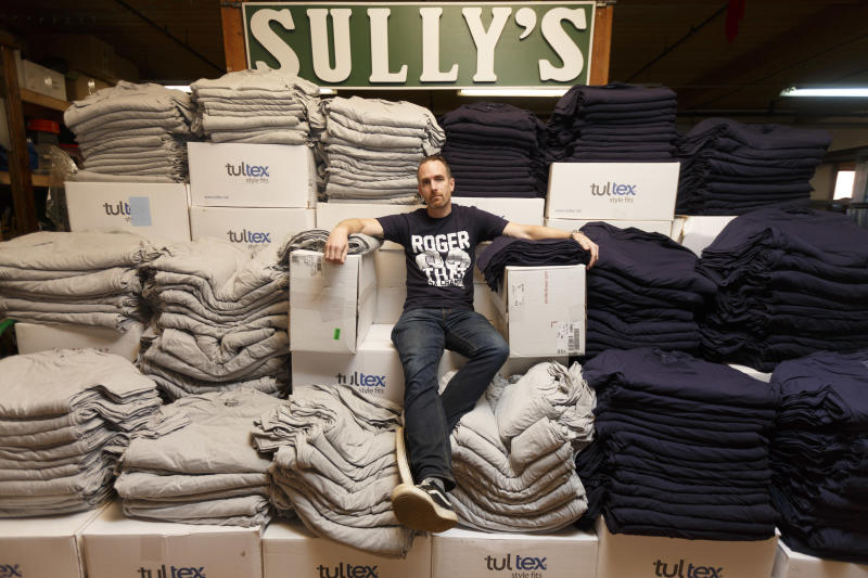 "PEABODY, MA - FEBRUARY 5: Chris Wrenn, founder of Sully's Brand sportswear, sits with piles of unprinted T-shirts purchased in anticipation of the New England Patriots Super Bowl victory that didn't happen in Peabody, MA on Feb. 5, 2018. He wears the iconic ""Roger That"" shirt that his company produced the previous year, which sold in massive numbers after one was held up by Patriots quarterback Tom Brady during the team's victory parade. This year, he plans to try to sell the unprinted shirts back to the distributor as a way to recoup his spent costs. (Photo by Dina Rudick/The Boston Globe via Getty Images)"