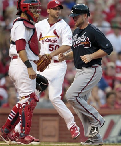 Atlanta Braves' Brian McCann, right, scores on a single by teammate Brandon Beachy as St. Louis Cardinals' Yadier Molina, left, and Adam Wainwright, center, cover home during the fifth inning of a baseball game on Saturday, May 12, 2012, in St. Louis. (AP Photo/Jeff Roberson)