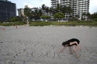 """Faydah Bushnaq, of Sterling, Va., writes """"Pray for their Souls"""" in the sand outside of a 12-story beachfront condo building which partially collapsed, Friday, June 25, 2021, in the Surfside area of Miami. Bushnaq is vacationing and stopped to write in the sand. The apartment building partially collapsed on Thursday. (AP Photo/Lynne Sladky)"""