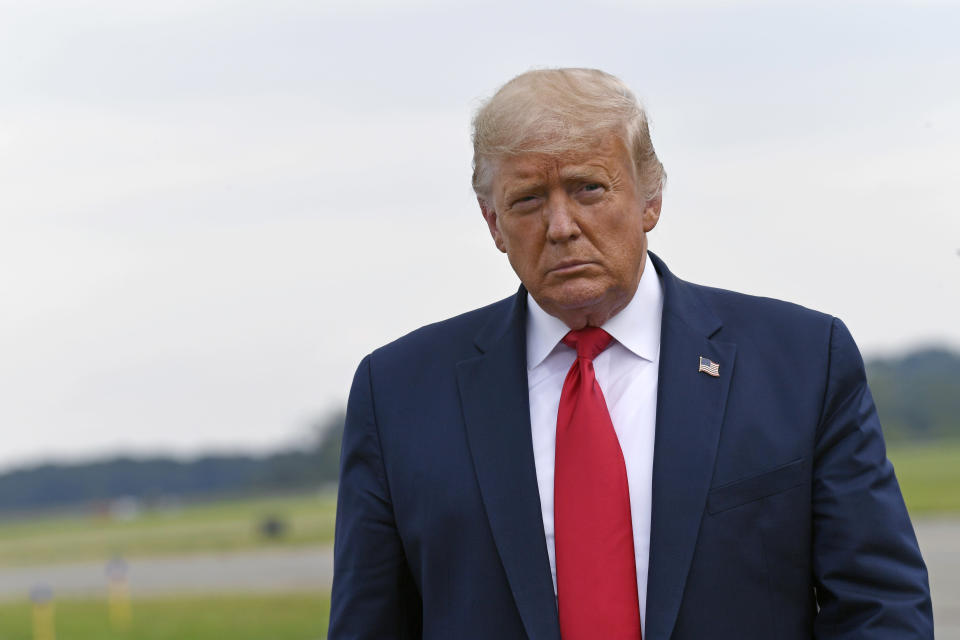 President Donald Trump walks over to speak with the press after arriving on Air Force One at Morristown Municipal Airport in Morristown, N.J., Friday, Aug. 14, 2020. Trump heading to New York to visit with his younger brother, Robert Trump, who has been hospitalized in New York. (AP Photo/Susan Walsh)