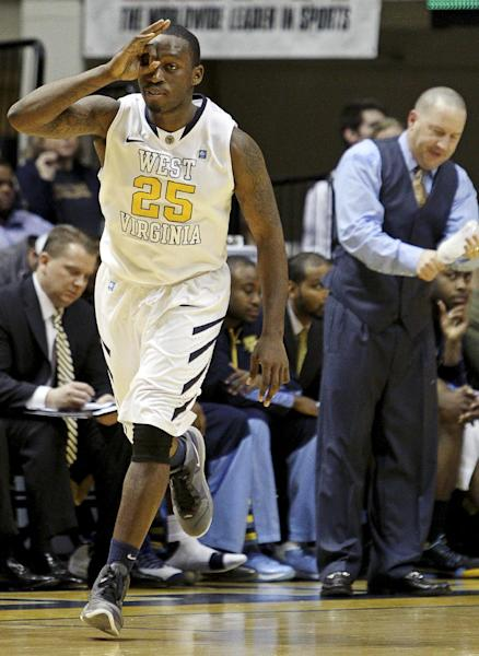 West Virginia's Darryl Bryant (25) celebrates a 3-pointer past Marquette coach Buzz Williams in the first half of an NCAA college basketball game, Friday, Feb. 24, 2012, in Morgantown, W.Va. (AP Photo/David Smith)