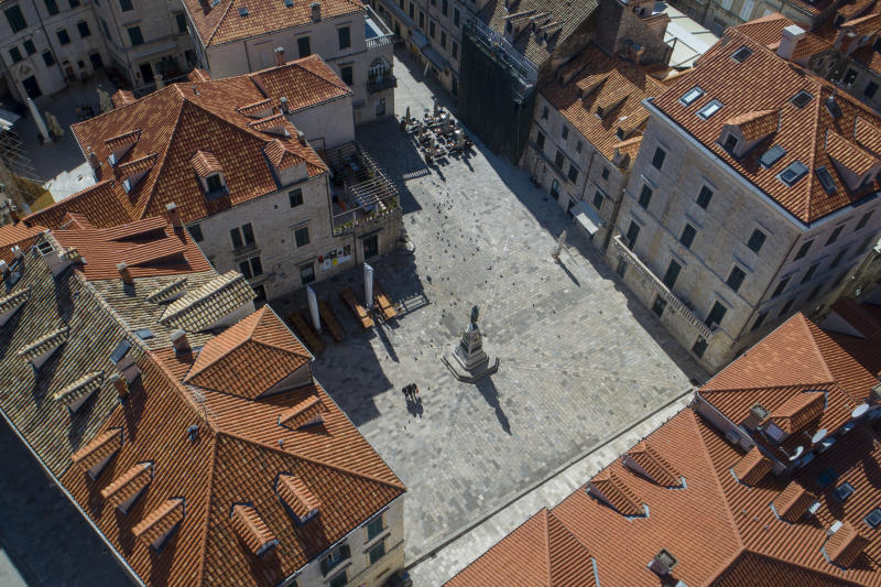 This aerial photo shows a square and restaurants in the medieval old town of Dubrovnik, Croatia, which would normally be full of tourists and residents, but now is empty due to travel and other restrictions because of the Coronavirus outbreak, Tuesday, March 17, 2020. For most people, the new coronavirus causes only mild or moderate symptoms but for some it can cause more severe illness. (AP Photo/Darko Bandic)