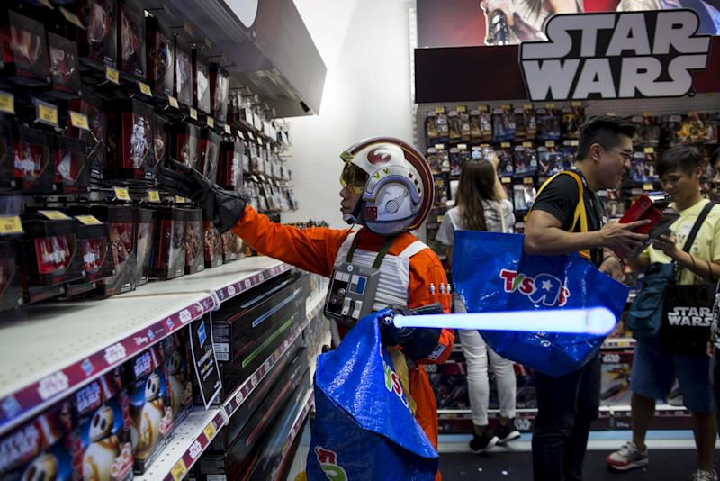 "FILE PHOTO - A fan dressed up as Luke Skywalker picks new toys from the upcoming film ""Star Wars: The Force Awakens"" on ""Force Friday"" after the launch of the film's new toys in Hong Kong, China, September 4, 2015.  REUTERS/Tyrone Siu/File Photo"