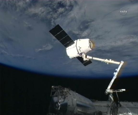 A SpaceX Dragon cargo capsule is perched at the end of the International Space Station's robotic arm after being grappled by astronauts on March 3, 2013, during the CRS-2 (SpaceX 2) cargo delivery mission.