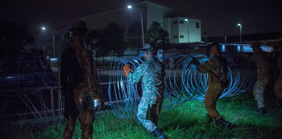 Military personnel install barbed wire around the Top Glove worker's hostel in Klang, Malaysia, on Nov. 17. (Photo: NurPhoto via Getty Images)