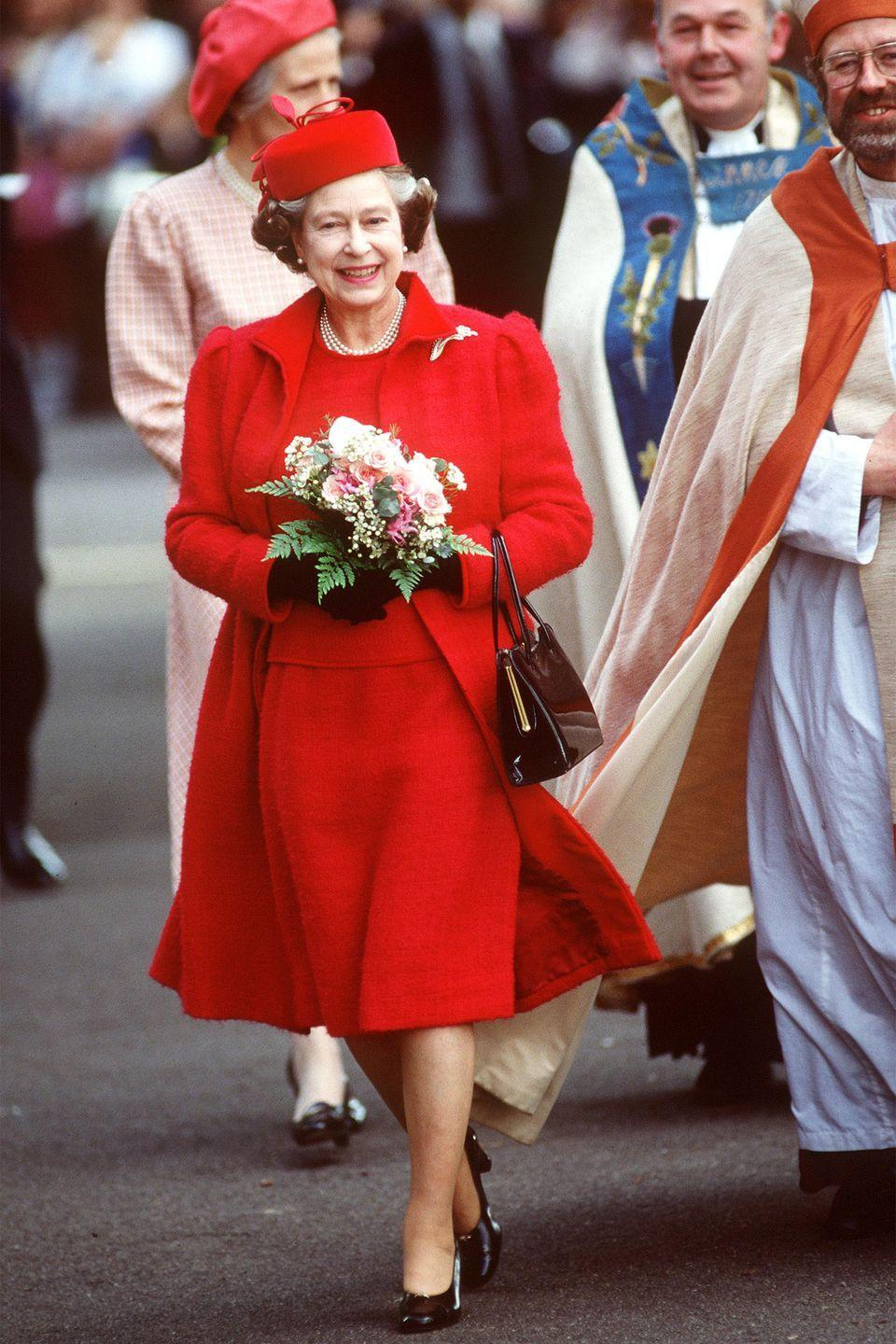 <p>She sports a red dress, coat, and matching pillbox hat for a visit to Saint Anne's Church.</p>