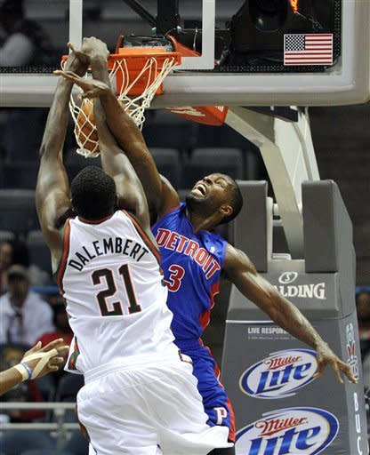 Milwaukee Bucks' Samuel Dalembert (21) dunks the ball over Detroit Pistons' Rodney Stuckey (3) during the first half of an NBA basketball game on Saturday, Oct. 13, 2012, in Milwaukee. (AP Photo/Jim Prisching)