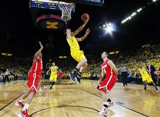 Michigan guard Zack Novak (0) shoots a layup between Ohio State guard Lenzelle Smith, Jr., left, and guard Aaron Craft, right, in the first half of an NCAA college basketball game, Saturday, Feb. 18, 2012, in Ann Arbor, Mich. (AP Photo/Tony Ding)