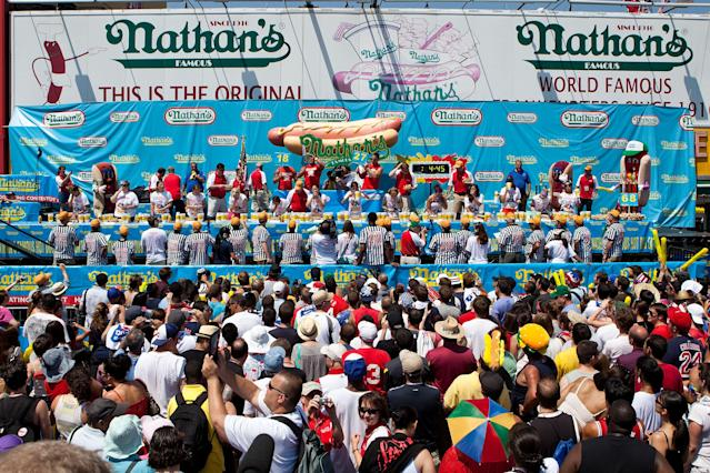 Women compete in the women's division of the Nathan's Famous International Hot Dog Eating Contest at Coney Island on July 4, 2012 in the Brooklyn borough of New York City. Sonya Thomas won the women's division by successfully eating 45 hot dogs in 10 minutes, setting a new world record. (Photo by Andrew Burton/Getty Images)