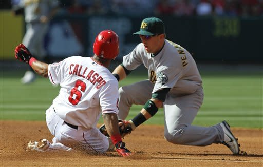 Oakland Athletics shortstop Cliff Pennington, right, tags out Los Angeles Angels' Alberto Callaspo at second after trying to stretch a single into a double during the first inning of a baseball game in Anaheim, Calif., Tuesday, May 15, 2012. (AP Photo/Chris Carlson)