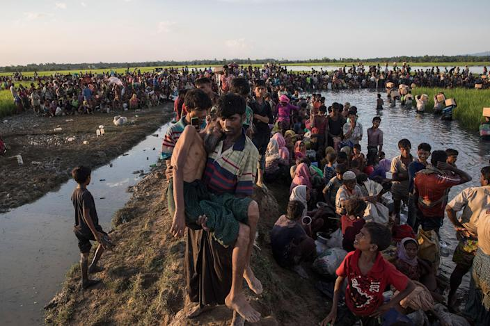 <p>An elderly man who collapsed is carried to a medical facility as thousands of Rohingya refugees fleeing from Myanmar sit along a muddy rice field after crossing the border near Palang Khali, Cox's Bazar, Bangladesh, on October 16, 2017. (Photograph by Paula Bronstein/Getty Images) </p>