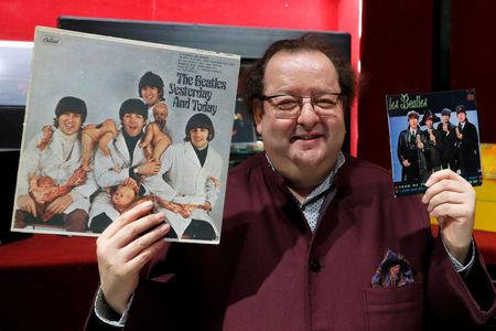 "French Beatles specialist and collector Jacques Volcouve, one of the world's greatest living experts of the band, poses with the ""Yesterday And today"" and ""From Me To You"" covers in Paris"