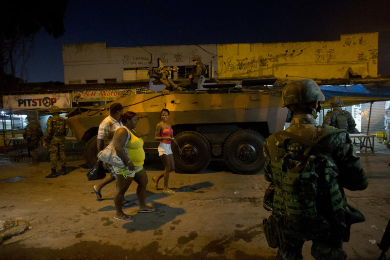 Residents walk past an armored vehicle during an operation to occupy the Mare slum complex in Rio de Janeiro, Brazil, Saturday, April 5, 2014. More than 2,000 Brazilian Army soldiers moved into the Mare slum complex early Saturday in a bid to improve security and drive out the heavily armed drug gangs that have ruled the sprawling slum for decades. (AP Photo/Silvia Izquierdo)