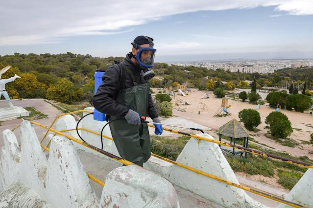 A health worker is pictured disinfecting the Enahli amusement park in Ariana near Tunis on 16 March. Tunisia has had 20 confirmed cases. (Getty Images)