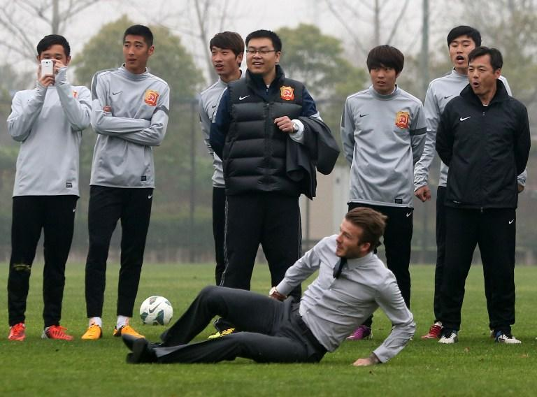 """Football superstar David Beckham (R) falls down after illustrating how to take a free kick during a visit to the Zall Football Club in Wuhan, central China's Wuhan province on March 23, 2013. Beckham raised the prospect of one last stop on his global football journey on March 20, refusing to rule out playing in China after his contract with Paris Saint-Germain ends. CHINA OUT AFP PHOTO"