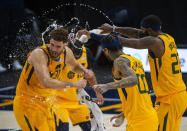 Utah Jazz's Mike Conley, rear, Royce O'Neale, right, and Jordan Clarkson (00) spray water on Utah Jazz forward Georges Niang (31) during his post-game interview following their NBA Basketball against the Charlotte Hornets Monday, Feb. 22, 2021, in Salt Lake City. (Rick Egan/The Salt Lake Tribune, via AP)