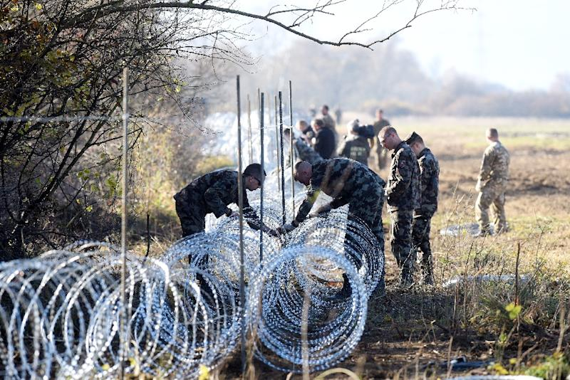 Slovenian soldiers set barbed wire fences on the Slovenian-Croatian border near Rakovec on November 12, 2015 (AFP Photo/STR)
