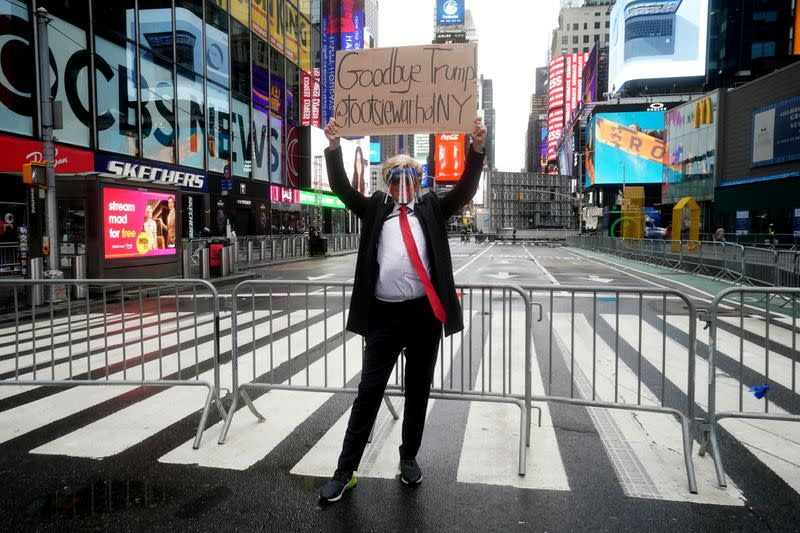 A Donald Trump impersonator poses for photos in Times Square ahead of New Year's Eve