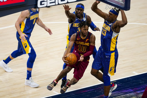 Cleveland Cavaliers guard Darius Garland (10) makes a pass around Indiana Pacers forward Myles Turner (33) during the second half of an NBA basketball game in Indianapolis, Thursday, Dec. 31, 2020. (AP Photo/Michael Conroy)
