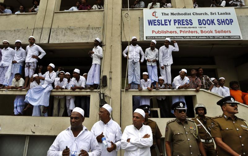 """Sri Lankan Muslims and police officers watch a protest outside the U.S. Embassy in Colombo, Sri Lanka, Monday, Sept. 24, 2012. Thousands of Sri Lankan Muslims protested against the American-produced film """"Innocence of Muslims"""" that ridicules Islam's Prophet Muhammad. (AP Photo/Eranga Jayawardena)"""