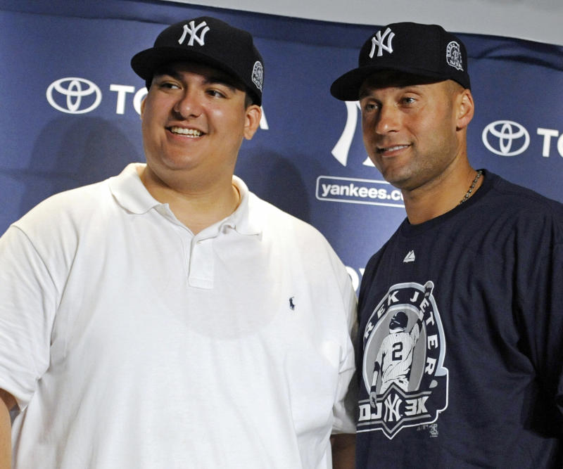 New York Yankees' Derek Jeter, right, poses with Christian Lopez  at a news conference after Lopez caught the 3,000 hit by Jeter during the third inning of a baseball game against the Tampa Bay Rays Saturday, July 9, 2011 at Yankee Stadium in New York. Lopez gave the ball to Jeter. (AP Photo/Bill Kostroun)